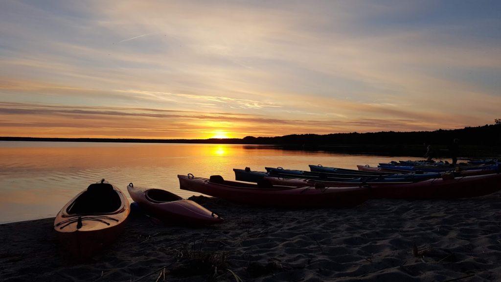 Kajaki rozłożone nad jeziorem, skąpane w świetle zachodzącego słońca.