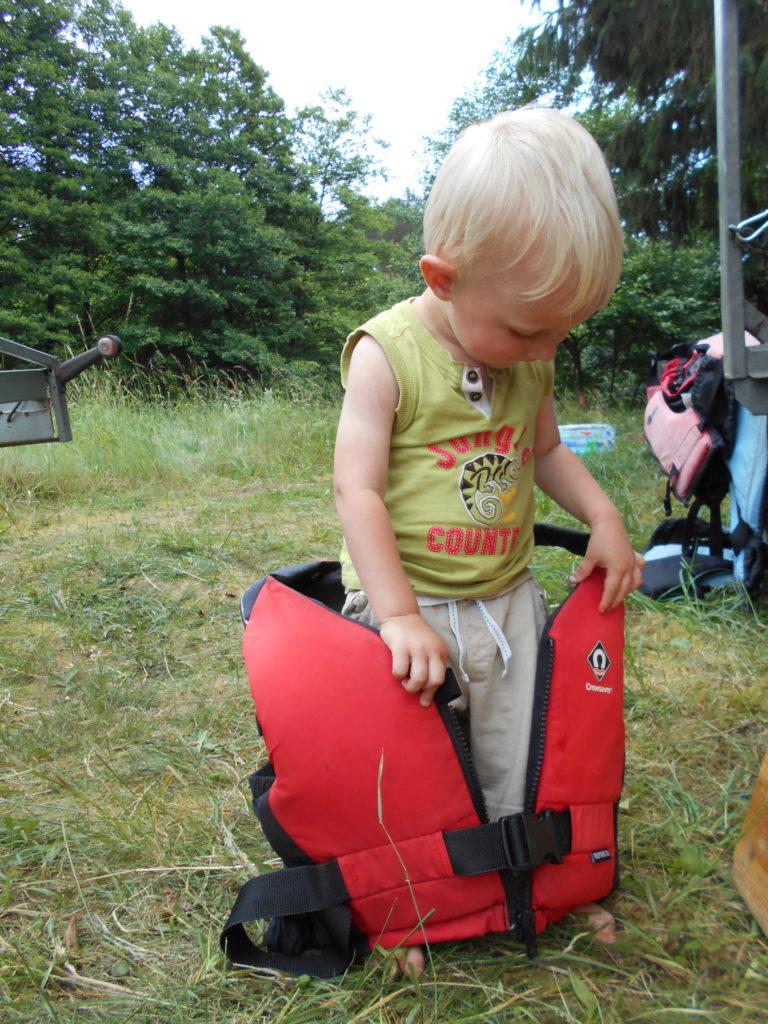 W ramach przygotowania do spływu, dziecko bawi się kamizelką asekuracyjną