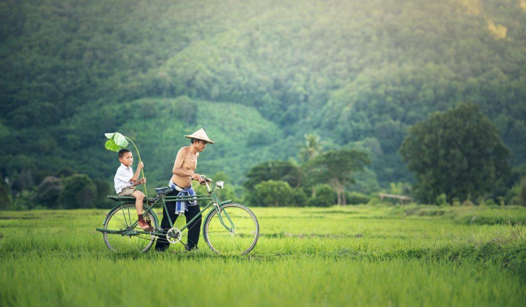 Ojciec wiezie syna na rowerze, pokazując mu świat