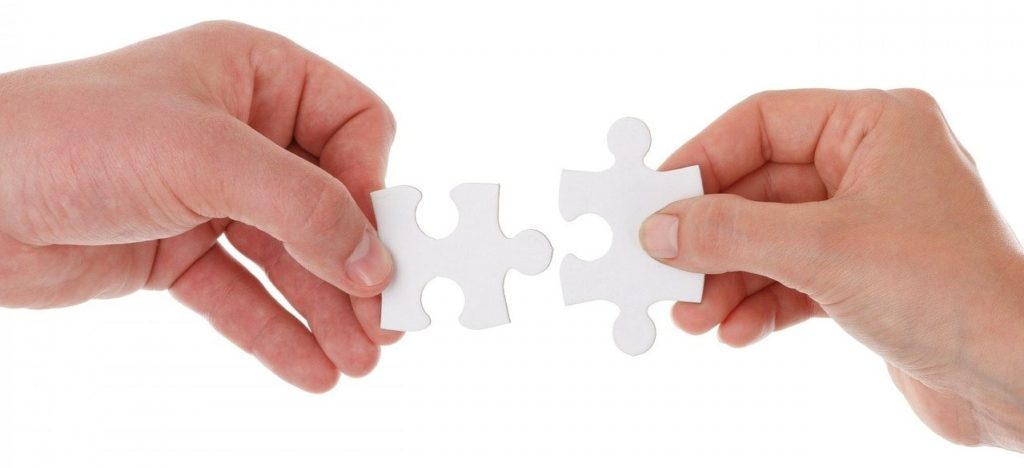 Ręce mężczyzny i kobiety trzymające pasujące do siebie puzzle jako obraz komplementarnej roli ojca i matki